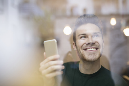 Cafe window view of happy mid adult man holding smartphone