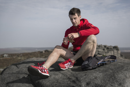 Male runner opening snacks on top of Stanage Edge,Peak District,Derbyshire,UK