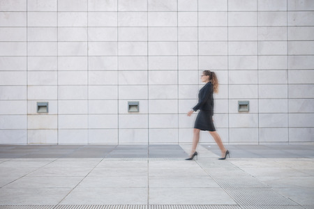 Young businesswoman walking outdoors,blurred motion