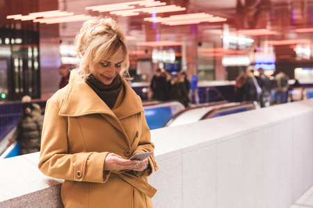 Woman looking at smartphone in underground station
