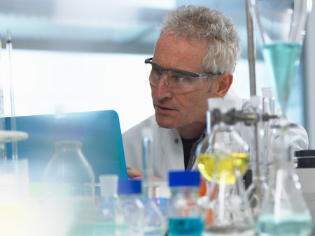 Scientist examining data on a laptop computer from an experiment in the laboratory LANG_EVOIMAGES