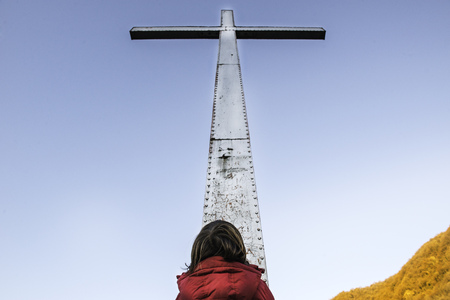 Rear view of boy looking up at towering cross and blue sky