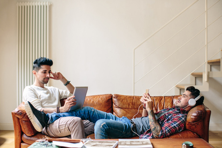 Male couple relaxing on sofa,wearing headphones,using smartphone and laptop