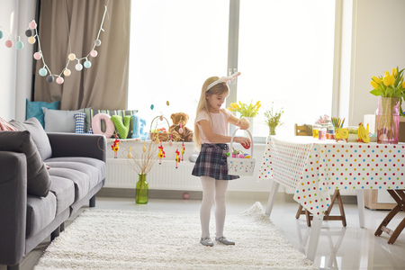 skirts: Girl placing easter eggs into basket in living room