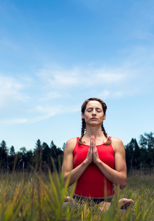 Young woman sitting in field, in yoga position LANG_EVOIMAGES
