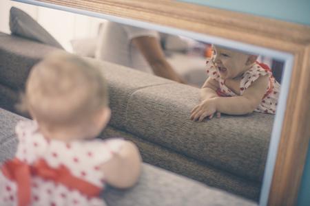 Mirror image of baby girl on sofa