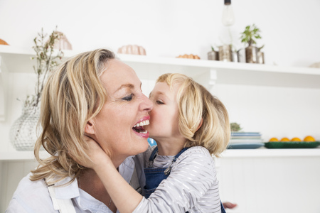 Girl kissing mother on cheek in kitchen