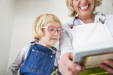 Mature woman sitting on kitchen counter reading storybook with daughter