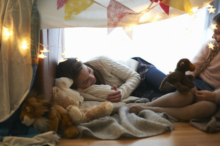 skirts: Two sisters in bedroom den lying down with soft toys
