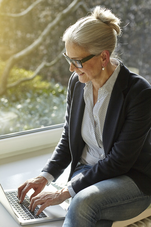 aging woman: Senior businesswoman typing on laptop at home on windowsill