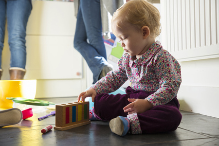 Baby girl sitting on kitchen floor playing with toys