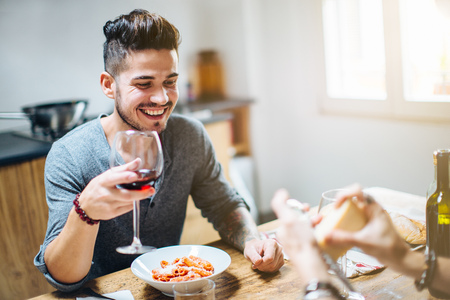 age 25 30 years: Male couple enjoying meal together,grating parmesan cheese on pasta,drinking wine