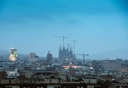 Elevated hazy cityscape view with La Sagrada Familia and construction cranes, Barcelona, Spain LANG_EVOIMAGES