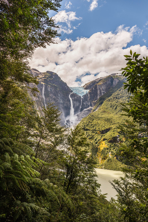 View of waterfall flowing from glazier at edge of  mountain rock face, Queulat National Park, Chile