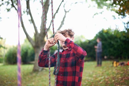 Trainee teenage male tree surgeon preparing climbing ropes