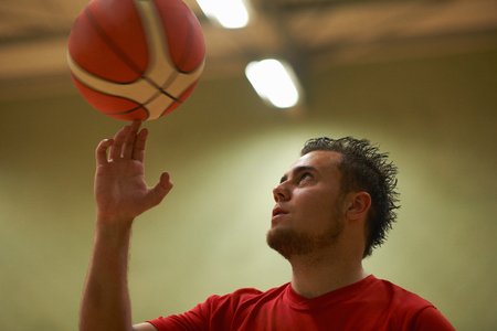 Student balancing basketball on fingertips LANG_EVOIMAGES