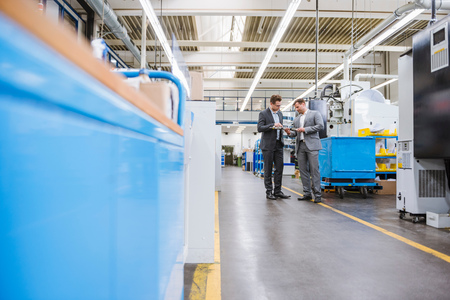 Factory managers inspecting product on factory production line