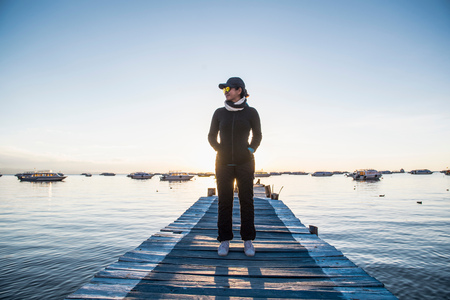 Woman standing on pier at Lake Titicaca, Copacabana, Bolivia LANG_EVOIMAGES