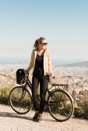 Woman sightseeing on bicycle, city in background, Barcelona, Catalonia, Spain