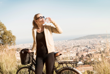 Woman drinking by bicycle, Barcelona, Catalonia, Spain