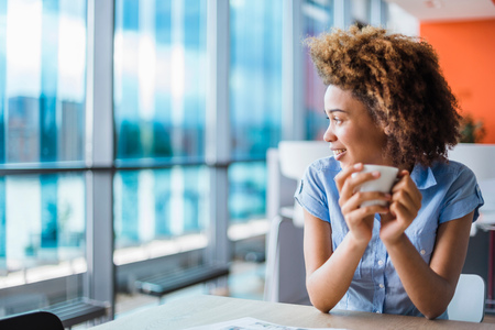 Young woman holding coffee at table gazing through window LANG_EVOIMAGES