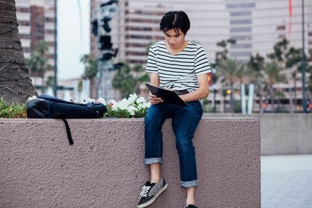 Young man sitting on wall, outdoors, writing in notebook