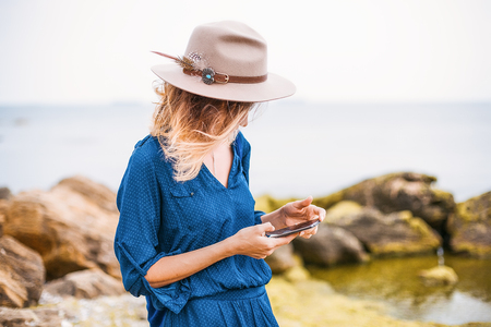 Mid adult woman in coastal setting, looking at smartphone