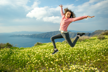 Girl jumping over flowers, O�a, Santorini, Kikladhes, Greece LANG_EVOIMAGES