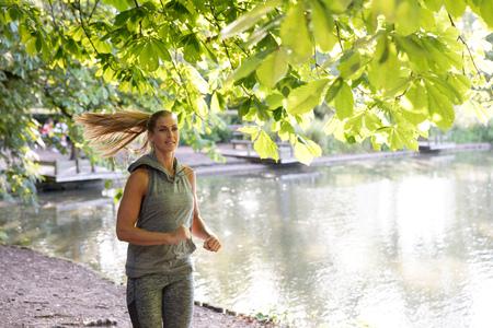 Młody żeński biegacza bieg parkowym jeziorem