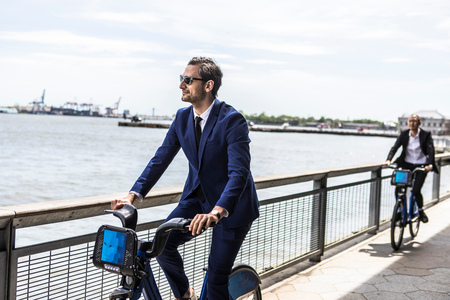 Young businessman cycling on waterfront, New York, USA
