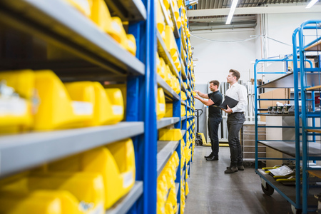 Male factory manager looking at warehouse shelves with worker in factory