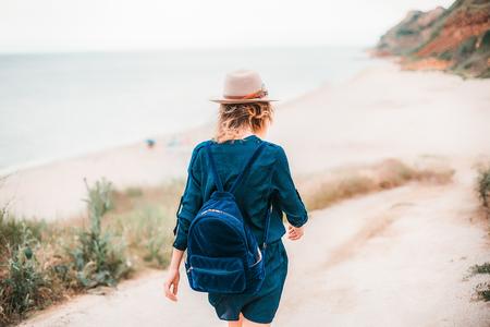 Mid adult woman walking towards beach, rear view