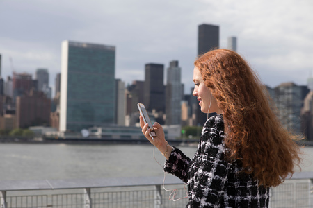 Young businesswoman on waterfront looking at smartphone, New York, USA