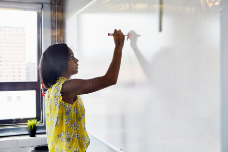 Young woman writing on whiteboard in office environment