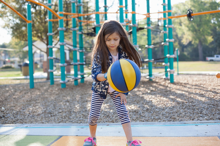 Girl bouncing basketball in playground LANG_EVOIMAGES