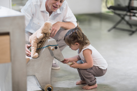 Father and baby girl looking at rocking horse LANG_EVOIMAGES