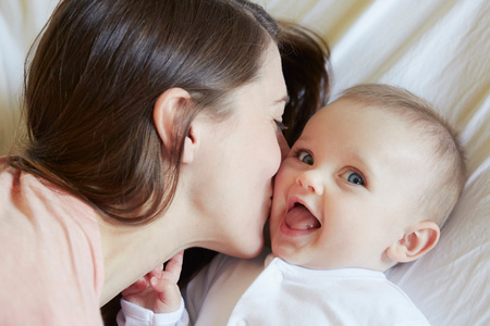Portrait Of Cute Baby Girl Being Kissed By Mother On Bed LANG_EVOIMAGES
