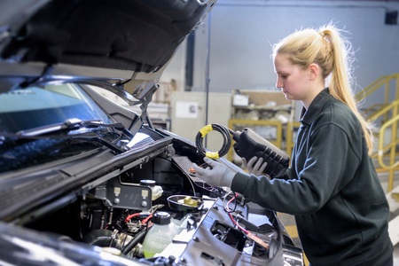 Female Apprentice Engineer Testing Car On Production Line In Car Factory