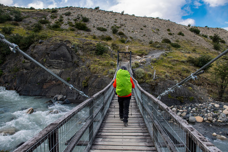 one mature woman only: Female Hiker Crossing A Suspension Bridge On The Way Up To Torres Del Paine National Park, Patagonia, Chile LANG_EVOIMAGES