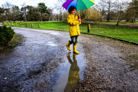only boys: Boy In Yellow Anorak Carrying Umbrella In Park