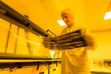 darkroom: Worker Inspecting Negative Of Circuit Board In Safe Yellow Light In Electronics Factory