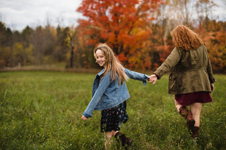 Mother And Daughter Holding Hands Walking In Meadow, Lakefield, Ontario, Canada