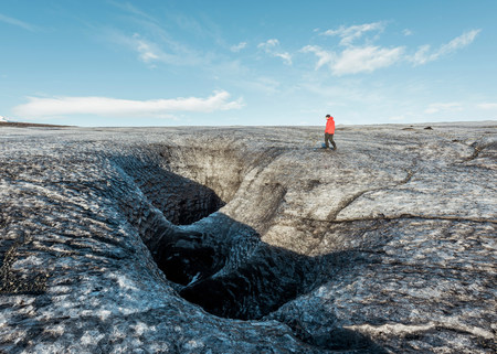 Male Tourist Walking By Glacial Crevice, South Iceland LANG_EVOIMAGES