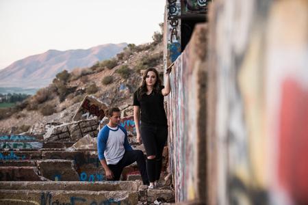 Hombre joven y mujer que exploran las paredes de Graffiti en la mina arruinada LANG_EVOIMAGES