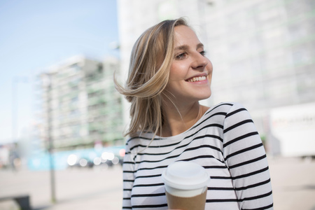 striated: Young Blond Haired Woman In City With Takeaway Coffee