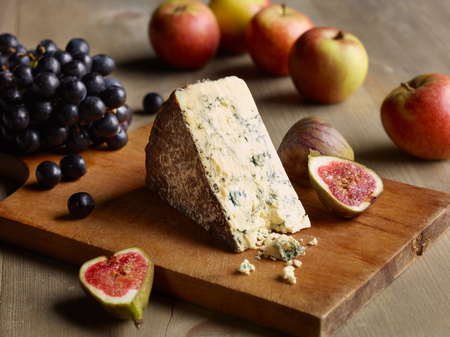 stilton: Still Life Of Stilton On Chopping Board With Figs, Apples And Grapes