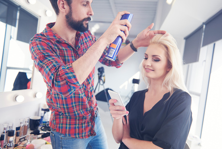 Male Hairdresser Putting Hairspray On Model For Photo Shoot LANG_EVOIMAGES