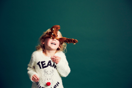 Portrait Of Young Girl Wearing Christmas And Reindeer Antlers LANG_EVOIMAGES