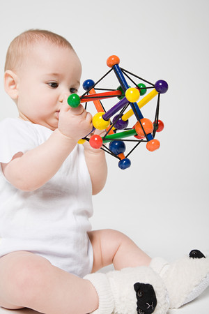 A Baby Boy Holding A Toy LANG_EVOIMAGES