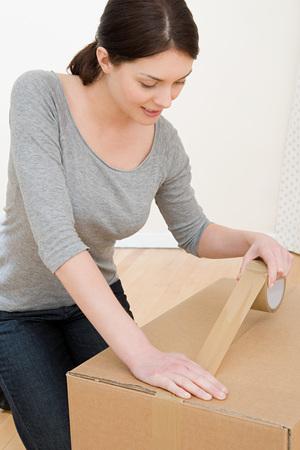 Kobieta Taping Up Box